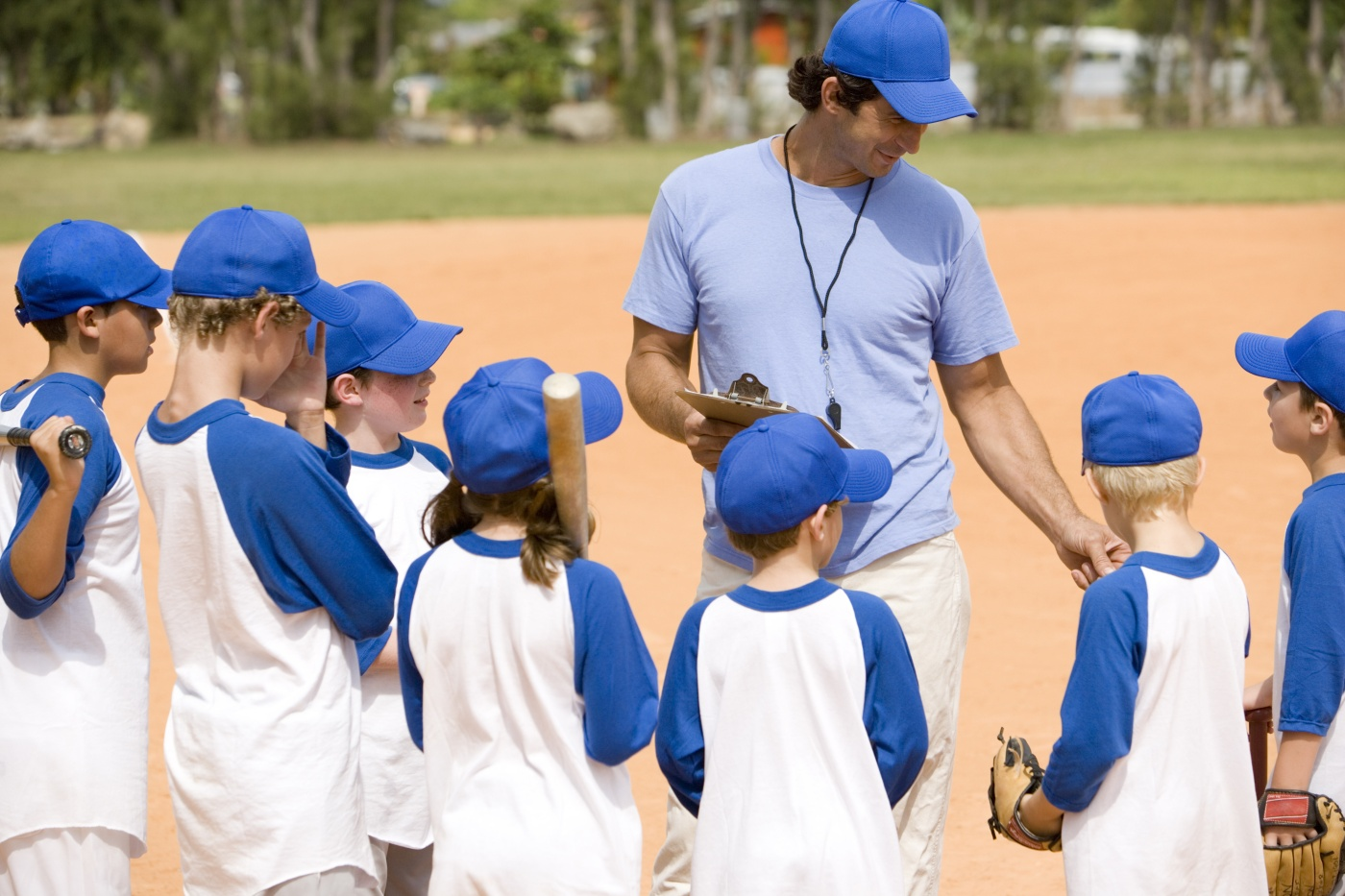 Little league baseball team and coach on pitch