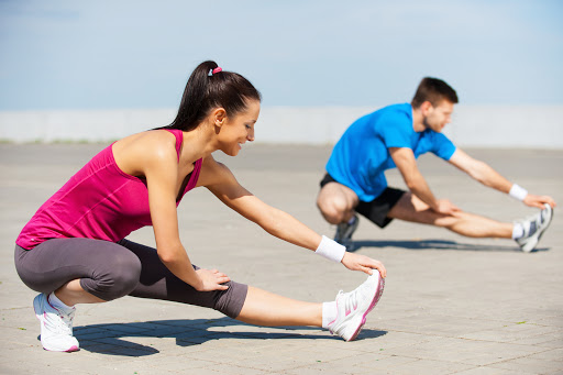 Exercising together is fun. Beautiful young woman and man doing stretching exercises together while standing outdoors